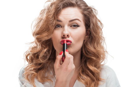 Woman applying lipstick and looking at camera