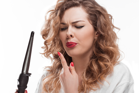 portrait of woman with curling iron in hand looking at burnt finger Stock Photo