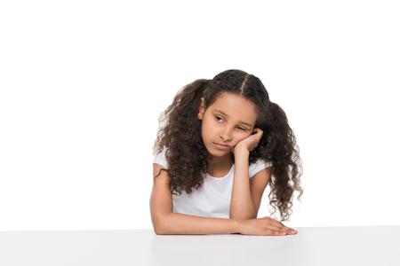 退屈の小さな女の子のテーブルに座って、よそ見の肖像画