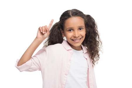 little girl pointing up with finger and smiling at camera