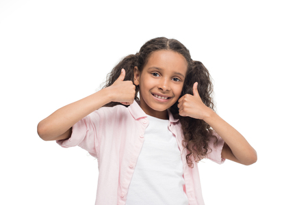 little girl showing thumbs up sign and smiling at camera