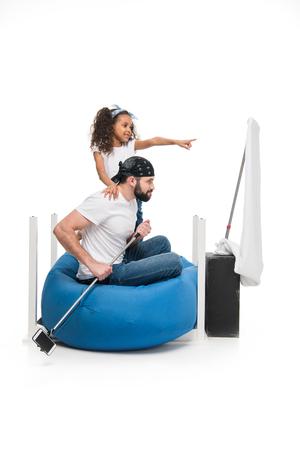 Zijaanzicht van vader en dochter die samen spelen alsof ze piraten zijn