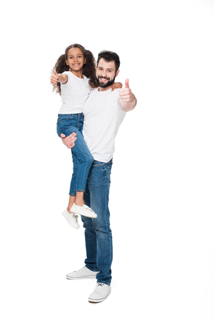 Happy father carrying adorable little daughter and showing thumbs up