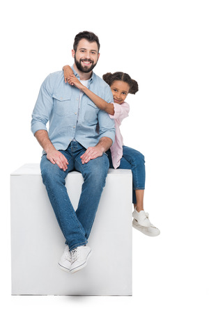 daughter hugging smiling father while sitting on cube together