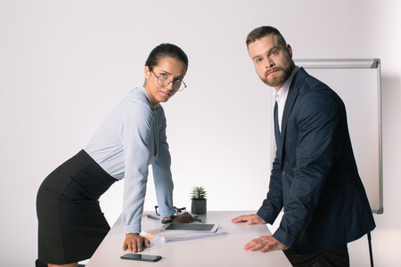 young business people leaning at office table and looking at camera