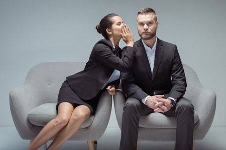 businesswoman whispering something on colleagues ear while sitting on chairs