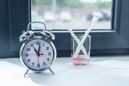 alarm clock and toothbrushes in glass at home