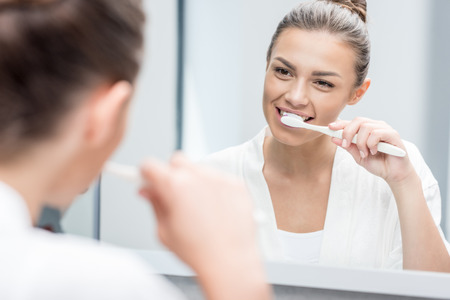 smiling woman brushing teeth with toothbrush at home