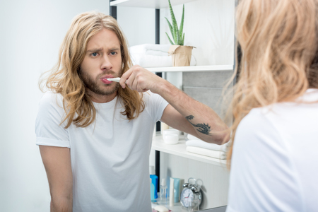 long haired man brushing teeth and looking at mirror