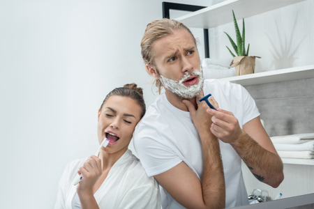 young man shaving beard with razor while happy woman singing in toothbrush
