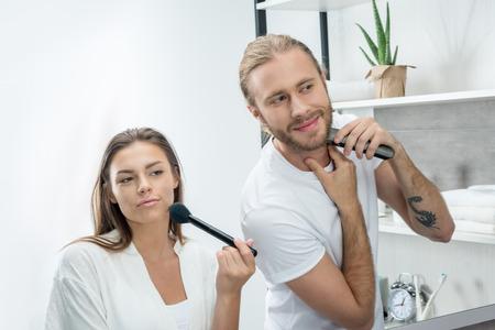 フェイス パウダーを適用する妻中のトリマーと男性シェービングひげ 写真素材