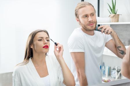 女性の朝夫シェービングひげながらマスカラーを適用します。 写真素材