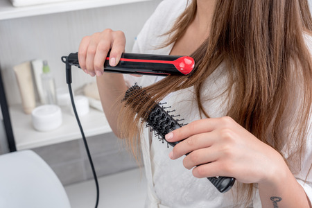 young woman in white robe using hair straightener in bathroom
