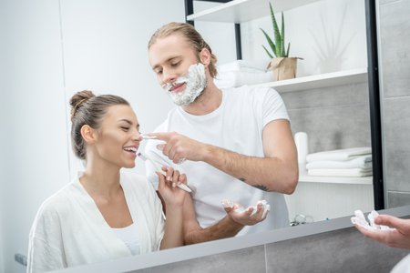 cheerful couple having fun while doing morning routine Stock Photo