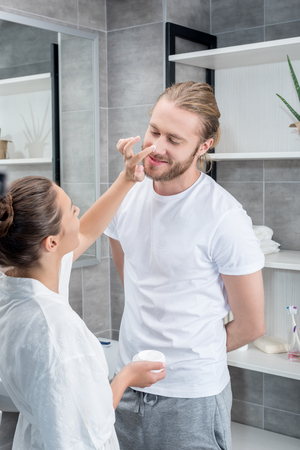 young wife applying face cream to husbands cheek in bathroom
