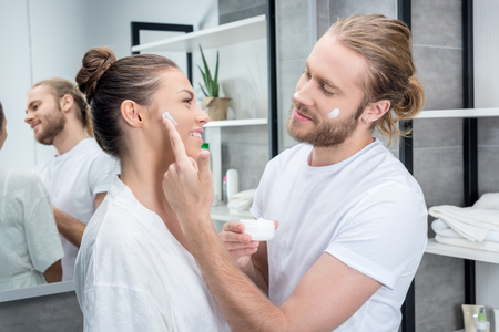 bearded husband applying face cream on cheek of his wife in bathroom Banco de Imagens