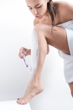 focused woman shaving legs after shower in morning