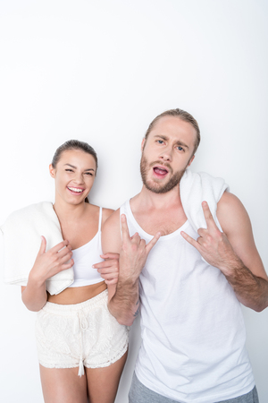man showing rock sign with smiling woman near by