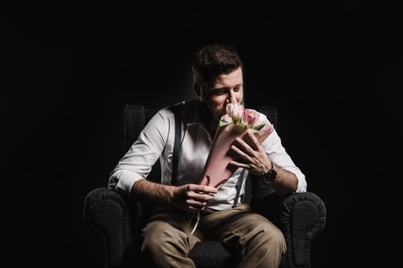 fashionable man sniffing tulip bouquet while sitting in armchair