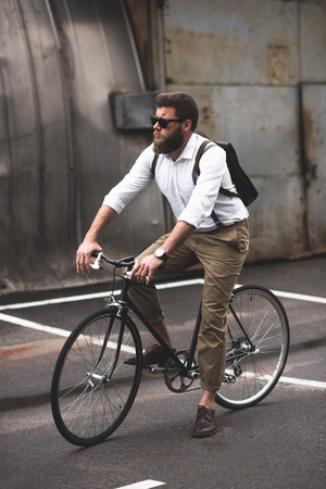 stylish bearded man in sunglasses riding bicycle