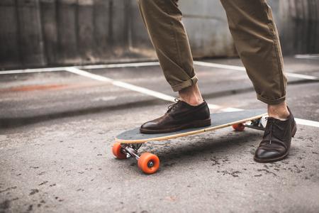 ロングボードと革靴でスタイリッシュな男の低いセクション 写真素材