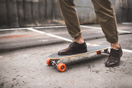 low section of stylish man in leather shoes with longboard Reklamní fotografie