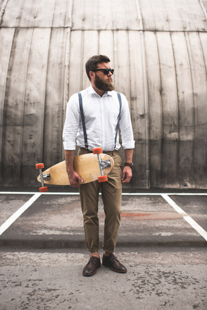 bearded man in white shirt and suspenders holding longboard on parking place