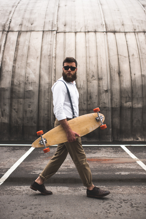bearded man in sunglasses walking with longboard on parking place