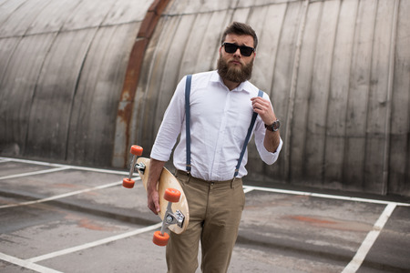 bearded man in sunglasses and suspenders holding longboard on parking place