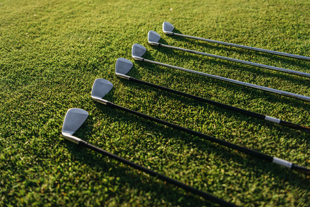 Shiny golf clubs arranged on the green grassy field