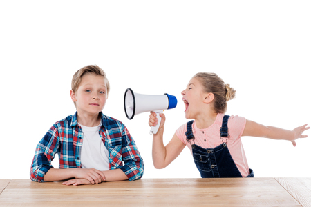 angry girl with megaphone yelling on her brother 版權商用圖片