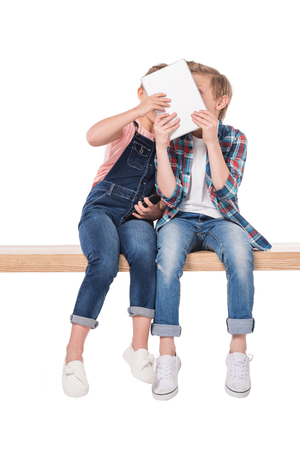cheerful boy and girl using digital tablet while sitting on bench,