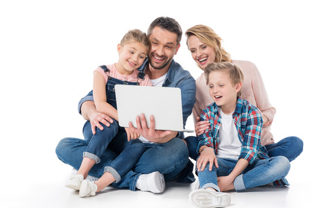 cheerful family using laptop while sitting on floor Banco de Imagens