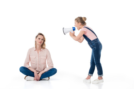 Little girl holding megaphone and screaming at pensive mother sitting Stock Photo