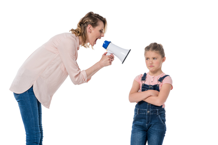 mother with megaphone screaming at little daughter standing with crossed arms