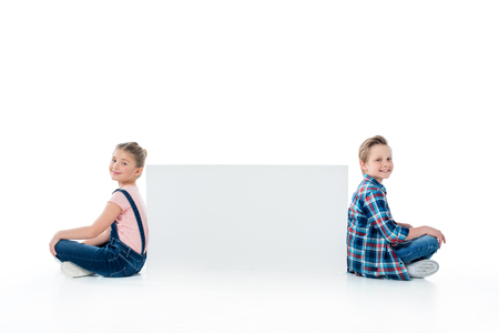 cute kids sitting with blank banner and smiling at camera
