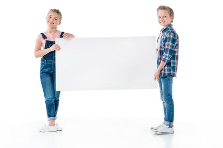 kleine kinderen die blanco banner houden en op camera lachen Stockfoto