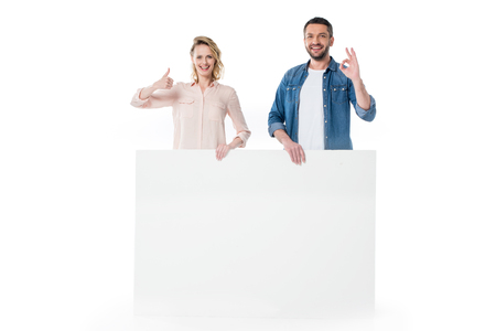 Happy young couple holding blank banner and gesturing successful sign Foto de archivo
