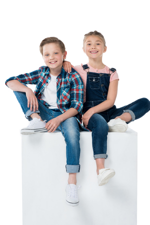 cheerful siblings sitting on cube together Stok Fotoğraf