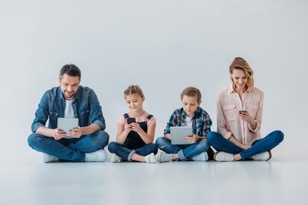 famille utilisant des appareils numériques assis sur le sol Banque d'images