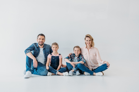 family looking at camera while sitting together on the floor Standard-Bild