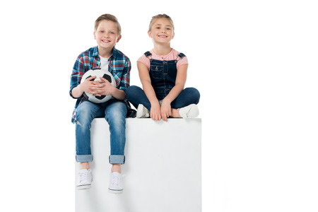 Boy with soccer ball in hands together with sister sitting on cube Stock Photo
