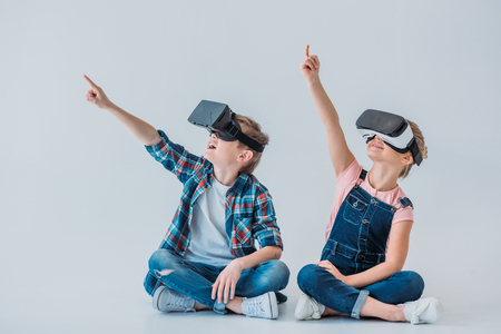 kids using virtual reality headsets and pointing up with finger while sitting