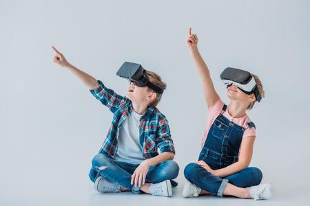 kinderen die virtuele reality headsets gebruiken en met vinger wijzen terwijl ze zitten