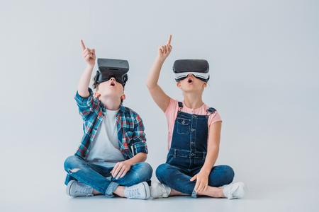 가상 현실 헤드셋을 사용하고 바닥에 앉아있는 동안 손가락으로 가리키는 아이들