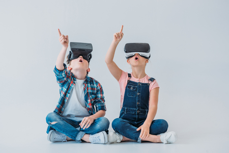 kids using virtual reality headsets and pointing up with finger while sitting on the floor Фото со стока