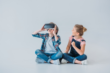 바닥에 앉아있는 동안 가상 현실 헤드셋을 사용하는 아이들