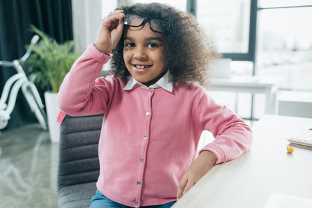 smiling african american girl with eyeglasses sitting in office Stock Photo