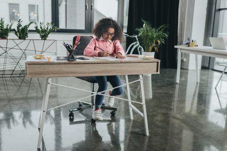 african american girl pretending to be businesswoman and working in modern office