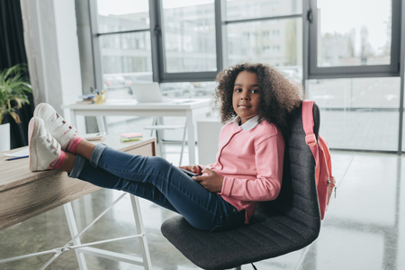 african american girl sitting on chair with legs on table in modern office
